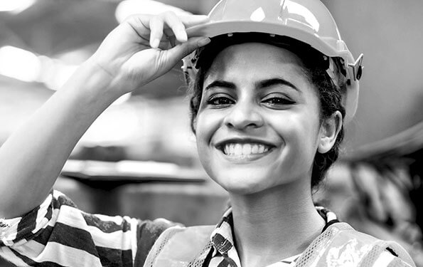 Smiling female worker in hard hat and reflective vest